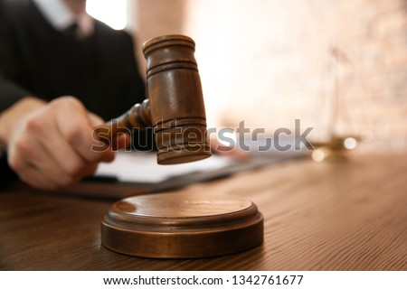 Judge with gavel at table in courtroom, closeup. Law and justice concept #1342761677
