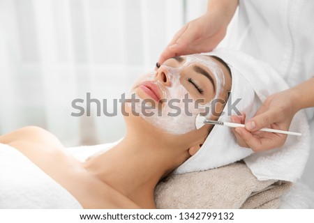 Cosmetologist applying mask on client's face in spa salon #1342799132