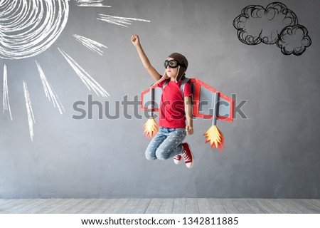 Happy child playing with toy jetpack. Kid pilot having fun at home. Success, innovation and leader concept #1342811885