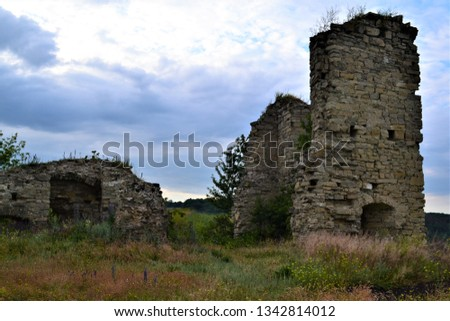 Ruins of a fortress on the background of a white blue sky. #1342814012