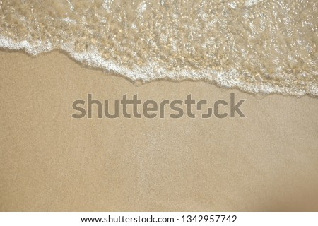 Soft wave of ocean on sandy beach background #1342957742