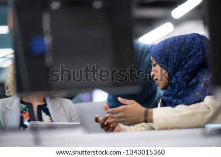 black muslim female software developer working together with her multiethnics business team using computer while writing programming code at modern startup office #1343015360