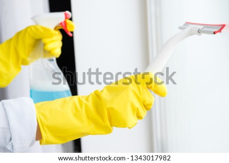 The girl washes the window at home #1343017982