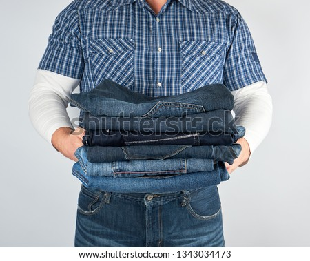 man in jeans and blue plaid shirt holding a pile of jeans on a white background #1343034473