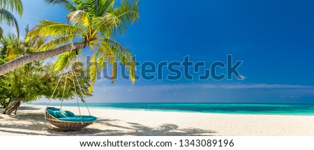 Tropical beach panorama as summer landscape with beach swing or hammock and white sand and calm sea for beach banner. Perfect beach scene vacation and summer holiday concept. Boost up color process #1343089196