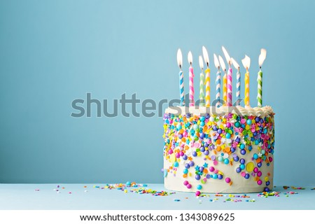 Colorful birthday cake with sprinkles and ten candles on a blue background with copyspace Royalty-Free Stock Photo #1343089625