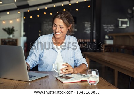 Smiling woman sitting in cafeteria holding coffee mug and working on laptop. Businesswoman checking email on laptop. Beautiful middle aged woman and using laptop at cafe while drinking a cup of tea. #1343163857
