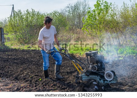 Man in wellingtons with cultivator ploughs ground in sunny day. Land cultivation, soil tillage. Spring work in garden. Gardening concept #1343255993