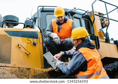 Worker sitting on heavy excavation machinery in mining operation #1343256593