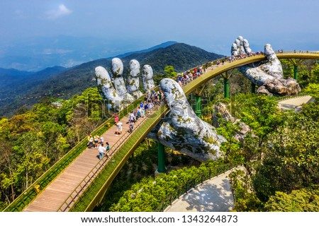 Aerial view of the Golden Bridge is lifted by two giant hands in the tourist resort on Ba Na Hill in Da Nang, Vietnam. Ba Na mountain resort is a favorite destination for tourists Royalty-Free Stock Photo #1343264873