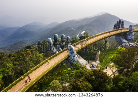 Aerial view of the Golden Bridge is lifted by two giant hands in the tourist resort on Ba Na Hill in Danang, Vietnam. Ba Na mountain resort is a favorite destination for tourists #1343264876