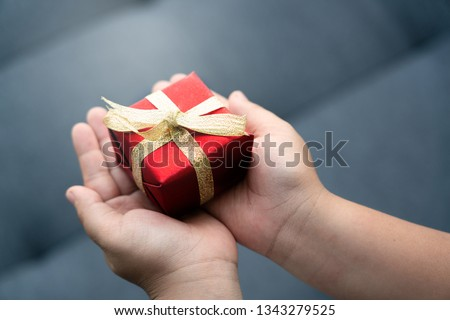Close up of a hand holding a red gift box tied with a gold ribbon. It is a joy to celebrate the holidays, such as Valentine's Day, Christmas and Happy New Year. Concept Universal Children's Day #1343279525
