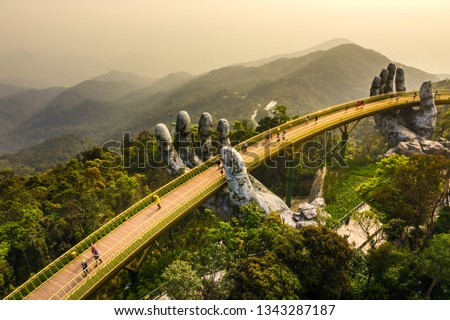"Top aerial view of the famous Golden Bridge is lifted by two giant hands in the tourist resort on Ba Na Hill in Da Nang, Vietnam. "" Cau Vang"" is a favorite destination for tourists   #1343287187"