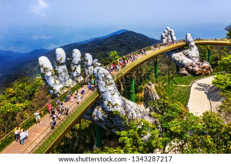 "Top aerial view of the famous Golden Bridge is lifted by two giant hands in the tourist resort on Ba Na Hill in Da Nang, Vietnam. "" Cau Vang"" is a favorite destination for tourists   #1343287217"