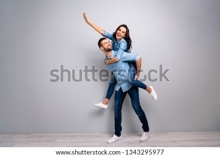 Full length body size photo funky cheer she her he him his lady guy piggyback ride walk meet adventures hand arm up run runner wear casual jeans denim shirts outfit clothes isolated grey background #1343295977
