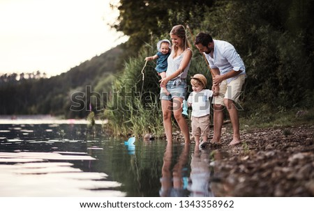 A young family with two toddler children outdoors by the river in summer. #1343358962