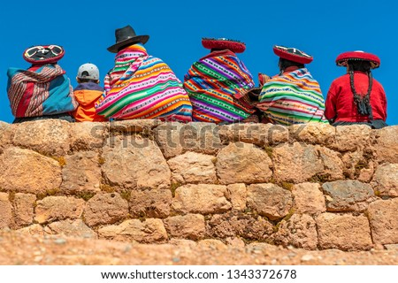 A group of Quechua indigenous women in traditional clothing and a young boy sitting and chatting on an ancient Inca wall in the archaeological site of Chinchero in the region of Cusco city, Peru. #1343372678