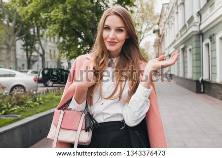 attractive stylish smiling woman walking city street in pink coat spring fashion trend holding purse, elegant style #1343376473