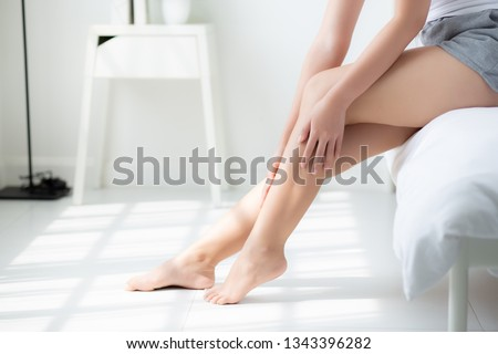 Beautiful closeup young asian woman sitting on a bed stroking legs with soft smooth skin in the bedroom, girl applying body cream and lotion with treatment, healthy and wellness concept. #1343396282
