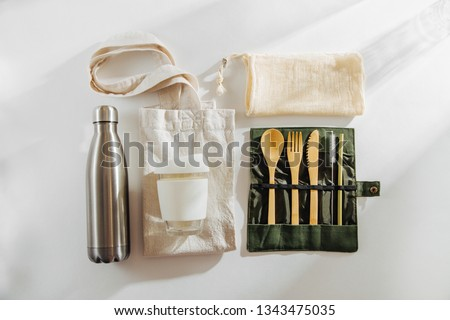 Set of Eco friendly bamboo cutlery, eco bag  reusable coffee mug  and  water bottle. Sustainable lifestyle.  Plastic free concept. Royalty-Free Stock Photo #1343475035
