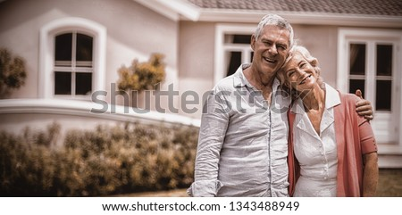 Smiling senior couple with arms around standing outside house in yard  #1343488949