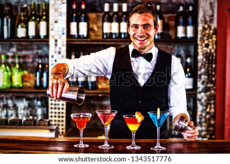 Portrait of bartender pouring a orange martini drink in the glass at bar #1343517776