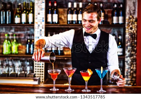 Bartender pouring a orange martini drink in the glass at bar #1343517785