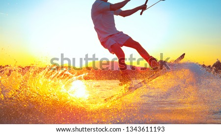 SUN FLARE, CLOSE UP: Cool surfer dude does 180 ollie while wakeboarding on a sunny summer evening. Cinematic shot of a cheerful man wakeboarding in the cool cable wake park. Awesome summer water sport #1343611193