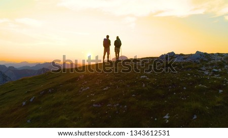 SILHOUETTE, AERIAL: Unrecognizable hikers watch the sunrise illuminate the picturesque Alps. Flying behind young woman and man stand on the mountaintop and observe the beautiful evening landscape. #1343612531