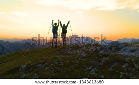 AERIAL: Unrecognizable young hiker couple outstretch arms as they catch the sunset while hiking in the Julian Alps. Picturesque shot of golden sunrise illuminating the excited male and female trekkers #1343613680