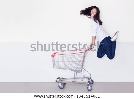 happy asian girl jump up shopping cart on white background. Potrait asian woman smile shoaholic with blank trolley for product display or sale festival concept. #1343614061