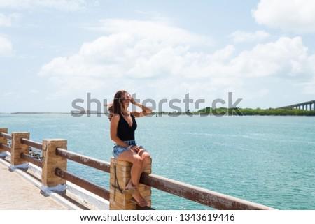 The beautiful tourist posing for photos in Redinha Beach (Natal) with  Potengi river and Newton Navarro bridge in background #1343619446