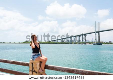 The beautiful tourist posing for photos in Redinha Beach (Natal) with  Potengi river and Newton Navarro bridge in background #1343619455