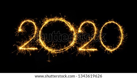 Happy New Year 2020. Number 2020 written sparkling sparklers isolated on black background With Copy Space For Text. Beautiful Glowing overlay template for holiday greeting card. Royalty-Free Stock Photo #1343619626