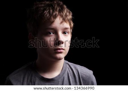 Portrait sad teenage boy on a black background #134366990