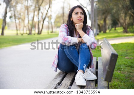 Serious attractive girl thinking about plans in park. Or she waiting for friend. Pretty woman sitting on bench and looking away. Contemplating concept