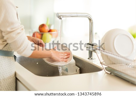 Housewife washing dishes in the kitchen sink Royalty-Free Stock Photo #1343745896