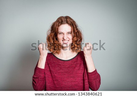 cute redhead girl rejoices victory with fists, isolated on gray background #1343840621