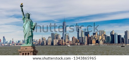 Panorama view of The Statue of Liberty with One World Trade Center and Manhattan downtown sky scraper with cloud blue sky background, Financial district lower Manhattan, New York City, USA. #1343865965