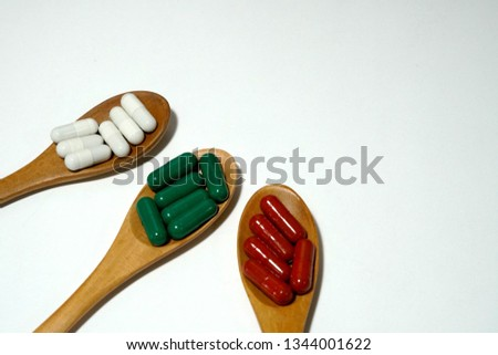 Herbal vitamins in capsule on wooden spoon and white background.  #1344001622