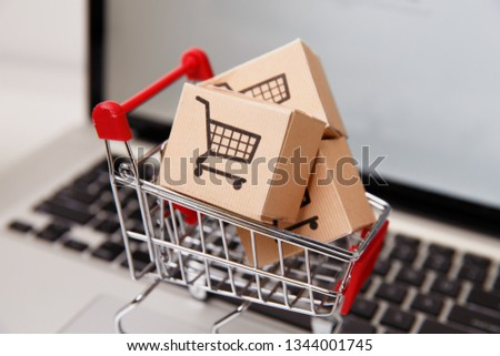 Many paper boxes in a small shopping cart on a laptop keyboard. Concepts about online shopping that consumers can buy things directly from their home or office just using a few clicks via web browser. #1344001745