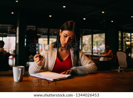 Young Brunette Woman is Working in the Cafe #1344026453