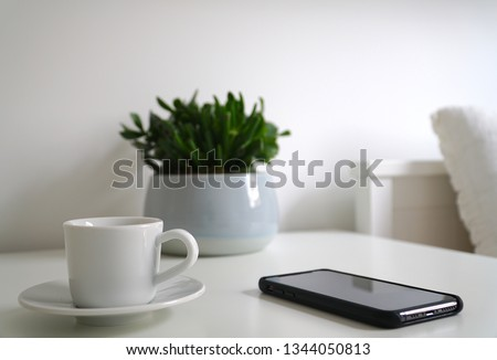 Close up white cup of coffee and mobile phone in bedroom in morning time with light from window.    #1344050813