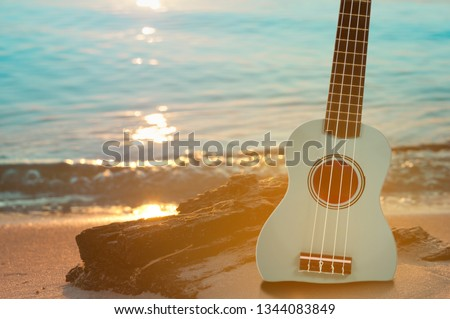 Guitar ukulele on sand beach with clear water and blue sky. Travel and lifestyle Concept. #1344083849