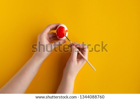 women's hands paint white chicken egg in red paint on a yellow background in the center diagonally #1344088760