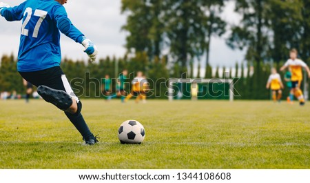 Soccer Football Goalkeeper Goal Kick. Goalie Kick on the Pitch During Match. Goalkeeper Restarting Play in a Game  #1344108608