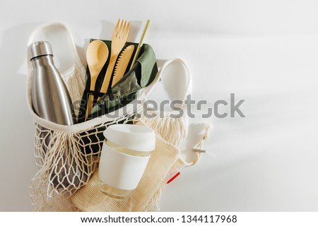 Mesh market bag with bamboo cutlery, reusable coffee mug  and  water bottle. Sustainable lifestyle.  Plastic free concept. Royalty-Free Stock Photo #1344117968