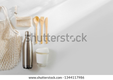 Set of Eco friendly bamboo cutlery, eco bag  reusable coffee mug  and  water bottle. Sustainable lifestyle.  Plastic free concept. Royalty-Free Stock Photo #1344117986