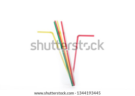 Transparent cup with colorful plastic straws isolated on the white background. Set for a birthday.  #1344193445