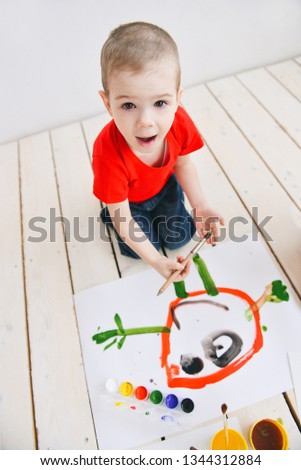 naughty creative children paint brush paints on paper funny colorful pictures on a wooden floor, art in a group art school. in a creative search for emotion